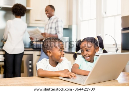 Siblings using laptop against parents in kitchen