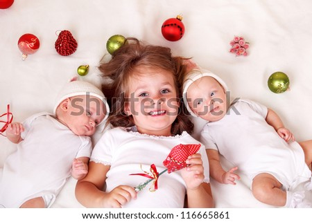 Siblings with Christmas decoration lie on bed - stock photo