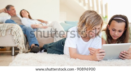 Siblings with tablet lying on the floor - stock photo