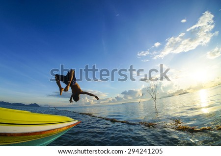 SIBUAN ISLAND, SABAH, MALAYSIA - JUNE 6 : Unidentified Sea Bajau's boy back-flip from the boat during sunrise June 6th, 2014 in Sibuan Island, Sabah Malaysia  - stock photo