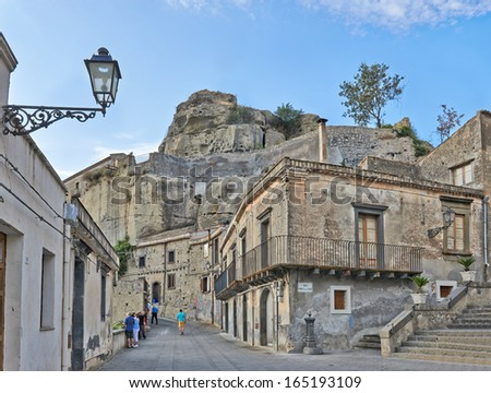 Sicily, Italy - SEPTEMBER 12, 2013: Tourist on the empty alley in the old small town in Sicily, Italy. To walk into this place is to walk back in time into the medieval era.   - stock photo