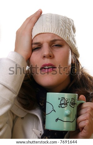 Sick A young woman is holding a cup of tea. She is sick and in pain with winter gear on. Isolated over white with space for text. - stock photo