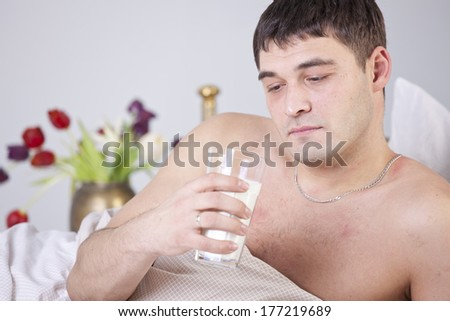 Sick and unhappy man with glass milk on bed