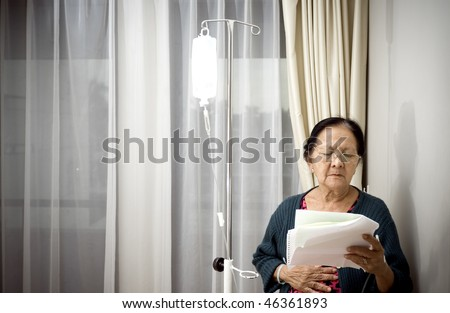 sick asian elderly woman during medication and inpatient treatment at the hospital. worried reading laboratory test result - stock photo