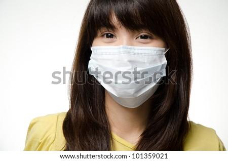Sick Asian girl on yellow shirt wear mask - stock photo