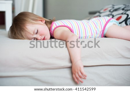 Sick baby girl lying in bed with a fever, resting at home - stock photo