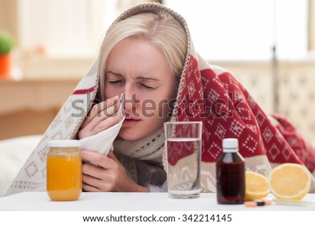 Sick blond girl has caught a cold. She is lying in bed and touching tissue to her nose. The lady closed her eyes with desperation. There are pills and vitamins on the table - stock photo