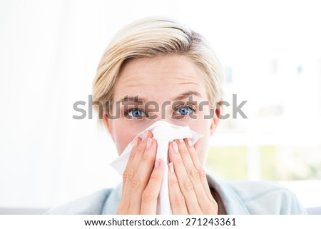 Sick blonde woman blowing her nose in the living room