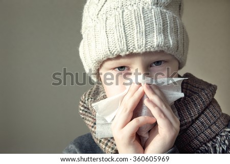 Sick boy (child, kid, teen) blowing his nose