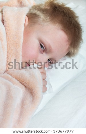 Sick boy (child, teen, kid) lying in bed, close up portrait with copy space - stock photo