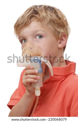 Sick boy inhales some medicine on white background - stock photo