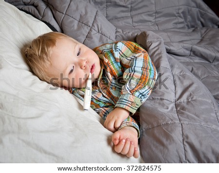 sick boy lying in bed with a thermometer in mouth - stock photo