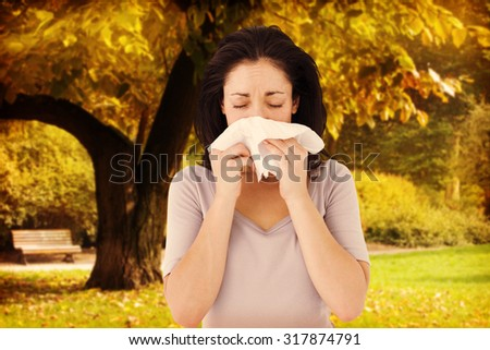 Sick brunette blowing her nose against trees and meadow in the park