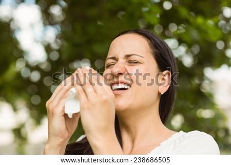 Sick brunette holding tissue sneezing in the park - stock photo