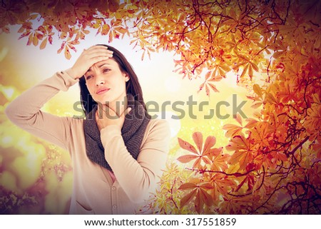 Sick brunette touching her throat and her head against autumn scene - stock photo