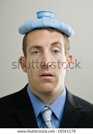 Sick businessman with headache using soothing ice pack on head