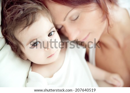 sick child and tired mother in bed, soft focus for tenderness. Shallow depth of field. FOcus on baby - stock photo