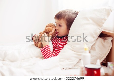 Sick child boy lying in bed with a fever, holding terry bear with band aid, resting - stock photo