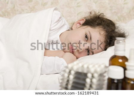 Sick child girl in a bed - stock photo