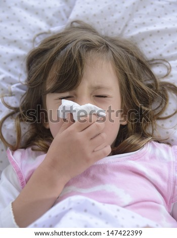 sick child in bed sneezing with tissue - stock photo