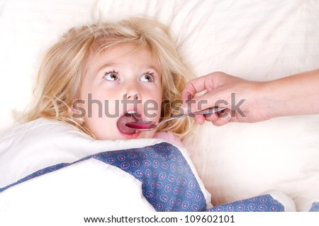 Sick child taking medicine from a spoon laying in bed