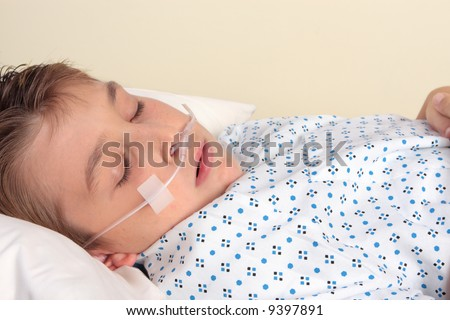 Sick child with nasal cannula.   a nasal cannula deliver  24% to 40% oxygen  Used for patients suffering respiratory disease, cardiac disease, shock, trauma, severe electrolyte imbalance (hypokalemia - stock photo