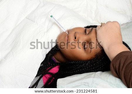sick child with thermometer in bed - stock photo