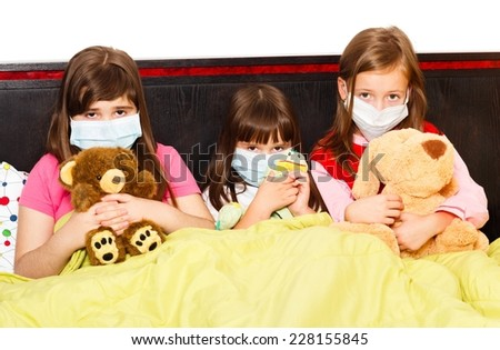 Sick children in bed wearing medical masks because of infection with influenza virus. - stock photo