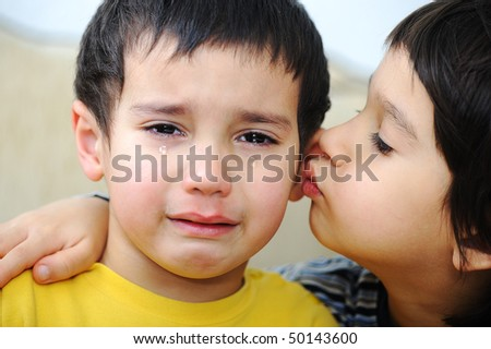 Sick crying kid and his brother - stock photo
