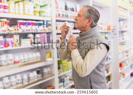 Sick customer holding a tissue in the pharmacy - stock photo
