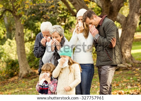 Sick family blowing their noses on an autumns day - stock photo