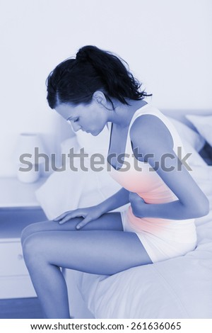 Sick feeling woman sitting on her bed in her bedroom - stock photo