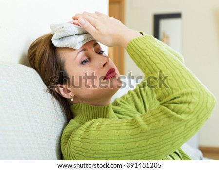 Sick  female with huge migraine holding wet towel on her head - stock photo