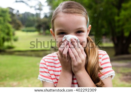 Sick girl covering her nose with tissue while sneezing in the park - stock photo