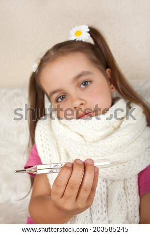 Sick girl in scarf with thermometer - stock photo