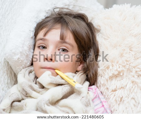 sick girl lying in bed with a thermometer in mouth - stock photo