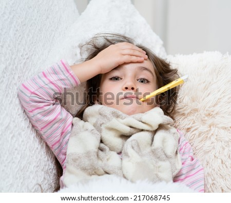 sick girl lying in bed with a thermometer in mouth and touch his forehead - stock photo