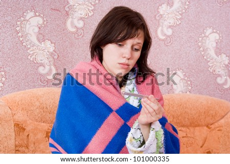 sick girl on the couch with a thermometer in her dressing gown - stock photo