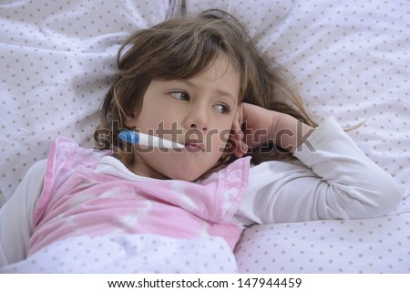 sick girl resting in bed with fever meassuring temperature with thermometer - stock photo