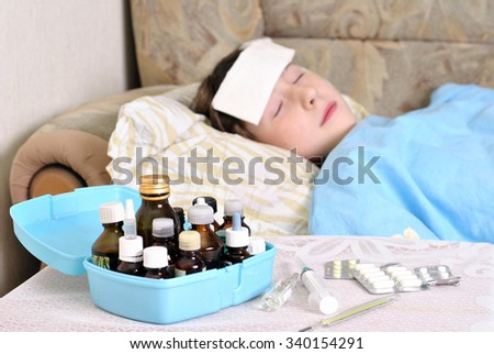 Sick girl sleeping in bed with medications on a bedside table - stock photo