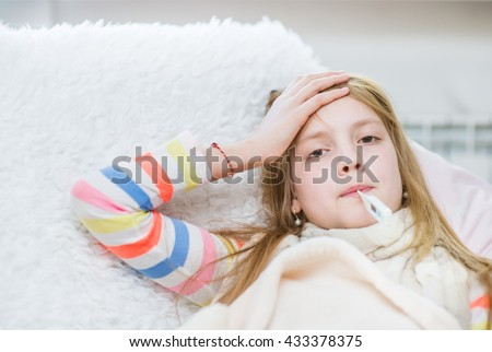 Sick girl with thermometer in mouth touching her forehead