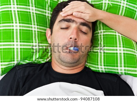 Sick hispanic man laying in bed with fever while a woman's hand touches his forehead - stock photo