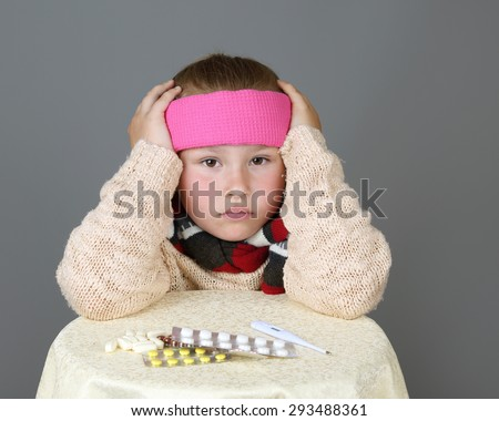 Sick in headband girl sits near table with medicine pills and holds head with hands on gray background - Headache, cold or disease concept - stock photo