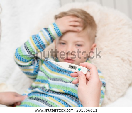 Sick kid with high fever laying in bed and mother checks the temperature - stock photo