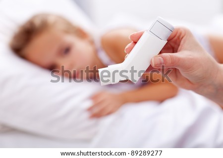 Sick kid with inhaler in foreground - asthma or other respiratory illness - stock photo