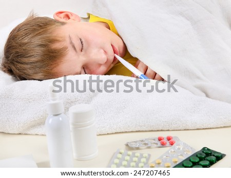 Sick Kid with Thermometer in the Bed - stock photo