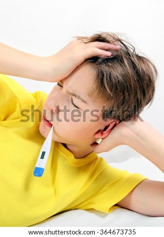 Sick Kid with Thermometer on the Bed - stock photo