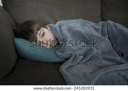 sick little boy laying on the sofa - stock photo