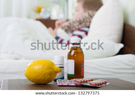 Sick little boy lying in bed. Pills and lemon on foreground. - stock photo