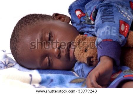 Sick little boy sleeping with his teddy bear - stock photo